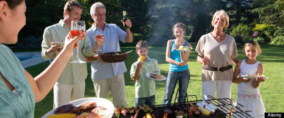 AHYDYR Three generation family standing beside barbecue grill in garden adults raising wine glasses in toast smiling